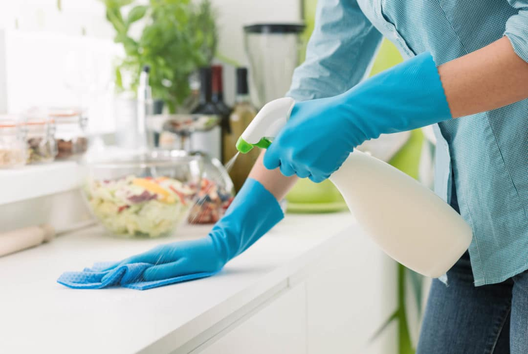 woman putting on blue cleaning gloves